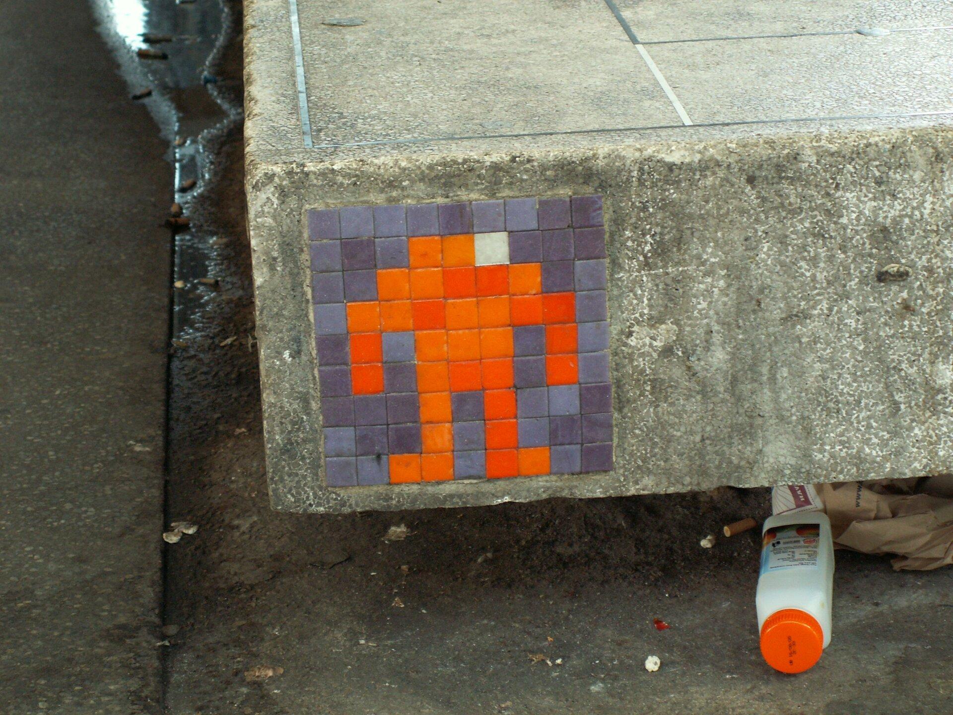Ilustracja przedstawia wlepkę ukazującą symbol ludzika złożonego zpomarańczowych kwadracików na szarym tle. Umieszczona jest na betonowej płycie.