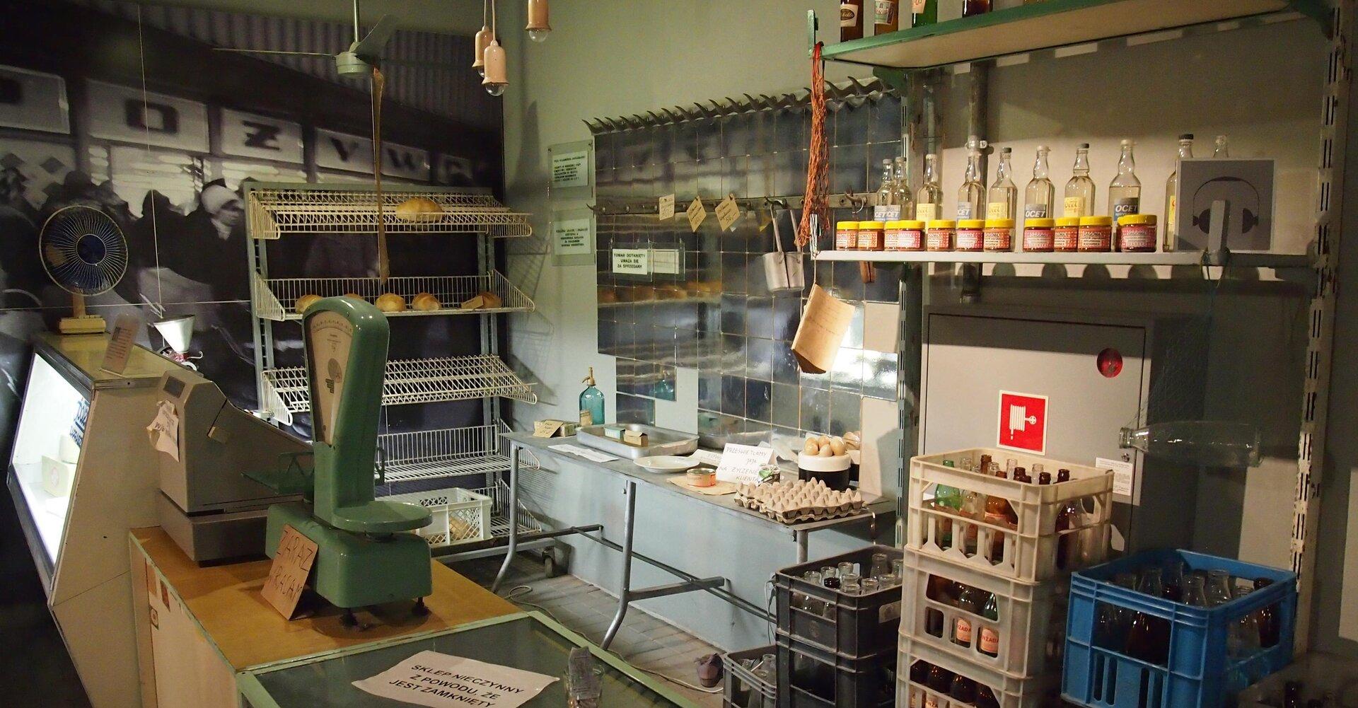 Fotografia barwna przedstawiająca wnętrze sklepu wczasach niedoboru ważnych produktów konsumpcyjnych. Puste półki, bardzo niewielka ilość chleba, jajek.