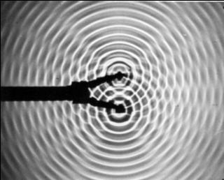 Fotografia cieniowa interferencji fal zdwóch źródeł punktowych na powierzchni wody. Na powierzchni wody są dwa punkty.