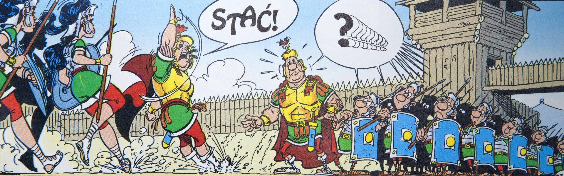 """Ilustracja przedstawia fragment komiksu """"Asterix. Róża imiecz"""". Ukazuje dwa oddziały wojowników zdowódcami na czele. Żołnierze idą ku sobie wszyku. Dowódca lewego oddziału podnosi wyprostowaną rękę. Od niego unosi się dymek ze słowem: Stać!. Nad prawym oddziałem oraz jego dowódcą unosi się dymek ze zwielokrotnionym znakiem zapytania. Wtle widoczna jest drewniany mur obronny zbramą iwierzą strażniczą. Nad nim rozciąga się błękitne niebo zchmurami."""