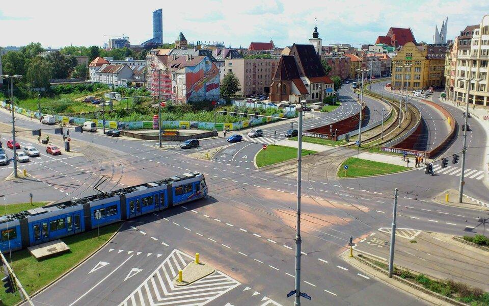 Na zdjęciu skrzyżowanie głównych ulic, tunel podziemny. Zabudowa zabytkowa, liczne wieże kościelne, wtle nowoczesne budynki.
