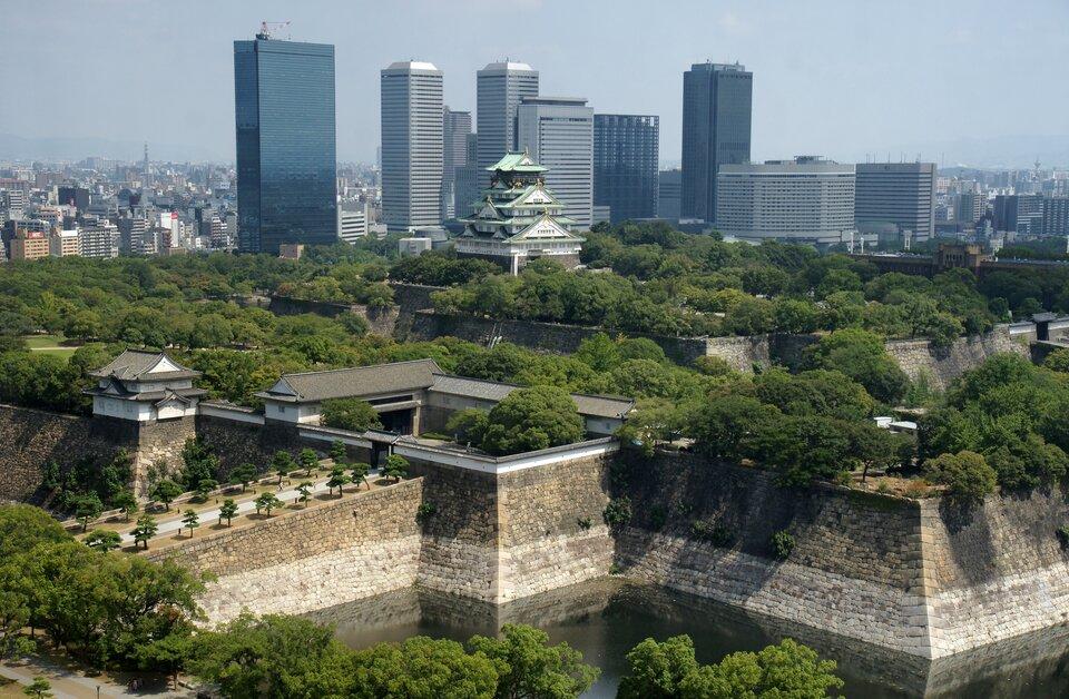 Na zdjęciu nowoczesne zabudowania biznesowe na tle charakterystycznej japońskiej świątyni zprzyległymi do niej rozległymi ogrodami.