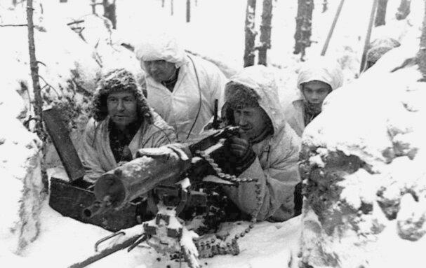 Czterej żołnierze wfutrzanych czapkach iwbiałych kombinezonach maskujących siedzą wokopie wlesie zasypanym śniegiem przy ciężkim karabinie maszynowym. Jeden zżołnierzy trzyma spust karabinu iceluje nim.