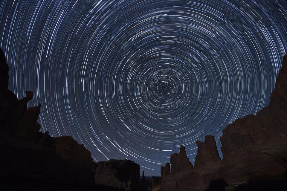 Zdjęcie przedstawia obraz nocnego nieba uzyskany znaświetlania klatki unieruchomionym aparatem przez godzinę. Skalisty krajobraz wdolnej części kadru ukazany jest normalnie, natomiast wobrębie nieba zamiast punktowych gwiazd widać jasne, koliste ślady pozostawione przez pozorny ruch ciał niebieskich po nieboskłonie. Jedynym nieporuszonym obszarem, wokół którego zachodzi ten obrót wydają się okolice Gwiazdy Polarnej, znajdującej się niemal dokładnie na przedłużeniu osi obrotu Ziemi, awięc nad Biegunem Północnym.
