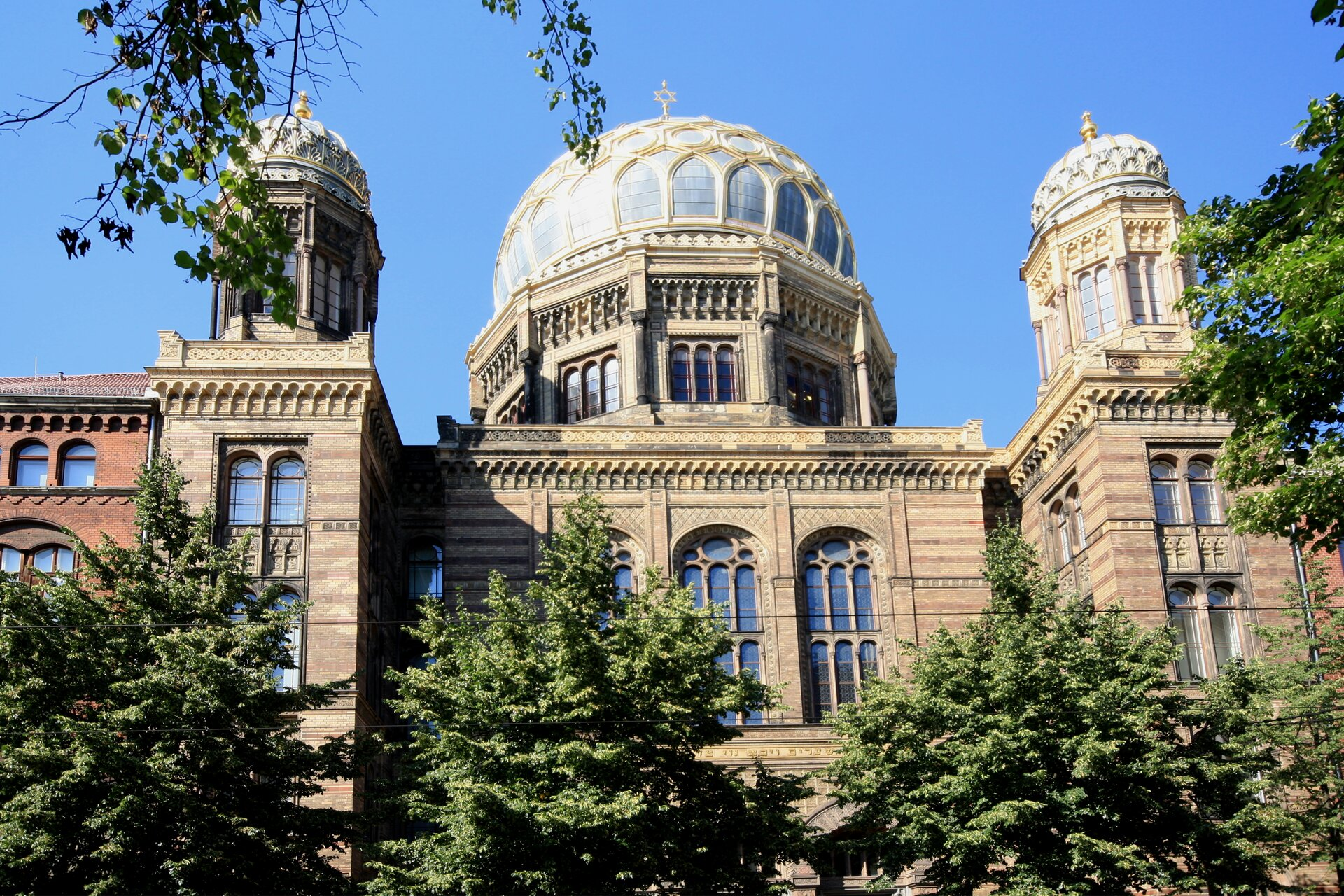 Na zdjęciu murowana synagoga wstylu mauretańskim, wschodnie detale iornamenty, trzy kopuły. Synagoga wciągu budynków. Na pierwszym planie drzewa.