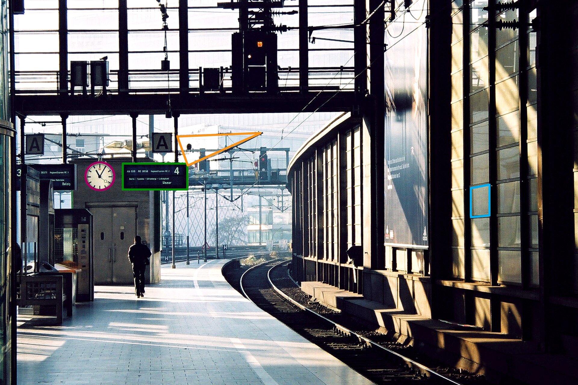 Zdjęcie stacji kolejowej. Kolorami zaznaczono okrągły zegar, prostokątną tablicę informacyjną, trójkątnie ułożone przewody iczworokątny element ściany.
