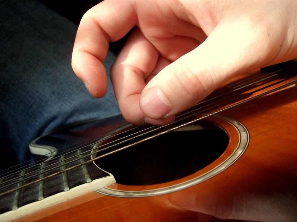 Zdjęcie przedstawia zbliżenie palców prawej ręki szarpiących struny gitary akustycznej zperspektywy osoby grającej na tę gitarze. Wtle materiał spodni, gitara oparta na nodze grającego. Wkadrze mieści się centralna część pudła oraz niewielki fragment gryfu.