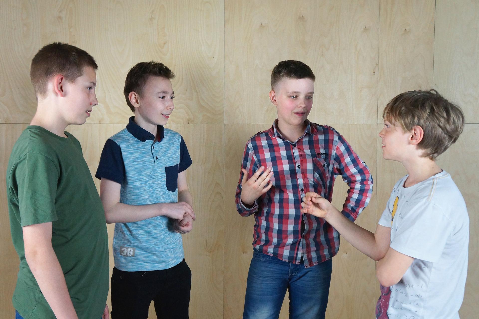 Galeria fotografii przedstawia etapy rozwoju człowieka od dojrzewania do starości. Fotografia przedstawia grupę czterech rozmawiających ze sobą chłopców wwieku około 12 lat. To okres, wktórym grupa rówieśników odgrywa dużą rolę wżyciu jednostki.