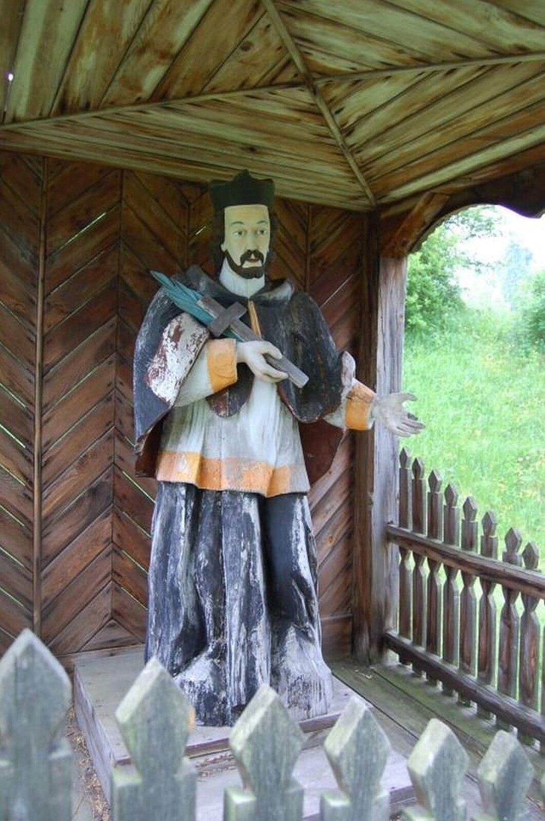 Ilustracja przedstawia figurę świętego Jana Nepomucena. Wdłoni trzyma krzyż ipalmę. Mężczyzna na głowie ma czarny biret. Brodaty mężczyzna ubrany jest wbiałą komżę oraz czarną sutannę. Figura umiejscowiona jest wdrewnianej kapliczce, otoczonej małym płotem.