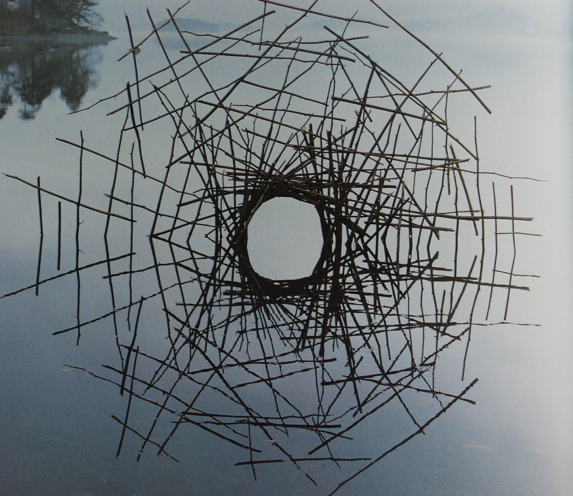 Ilustracja przedstawia budowlę, zpatyków, która znajduje się nad taflą zbiornika wodnego. Ważnym elementem twórczości artysty jest przemijanie. Wiele jego prac ulega zmianie idestrukcji pod wpływem pogody, czasu, krajobrazu. Użyte materiały są nietrwałe lub umieszczone wtakich miejscach, wktórych zostaną zniszczone przez działanie przyrody.