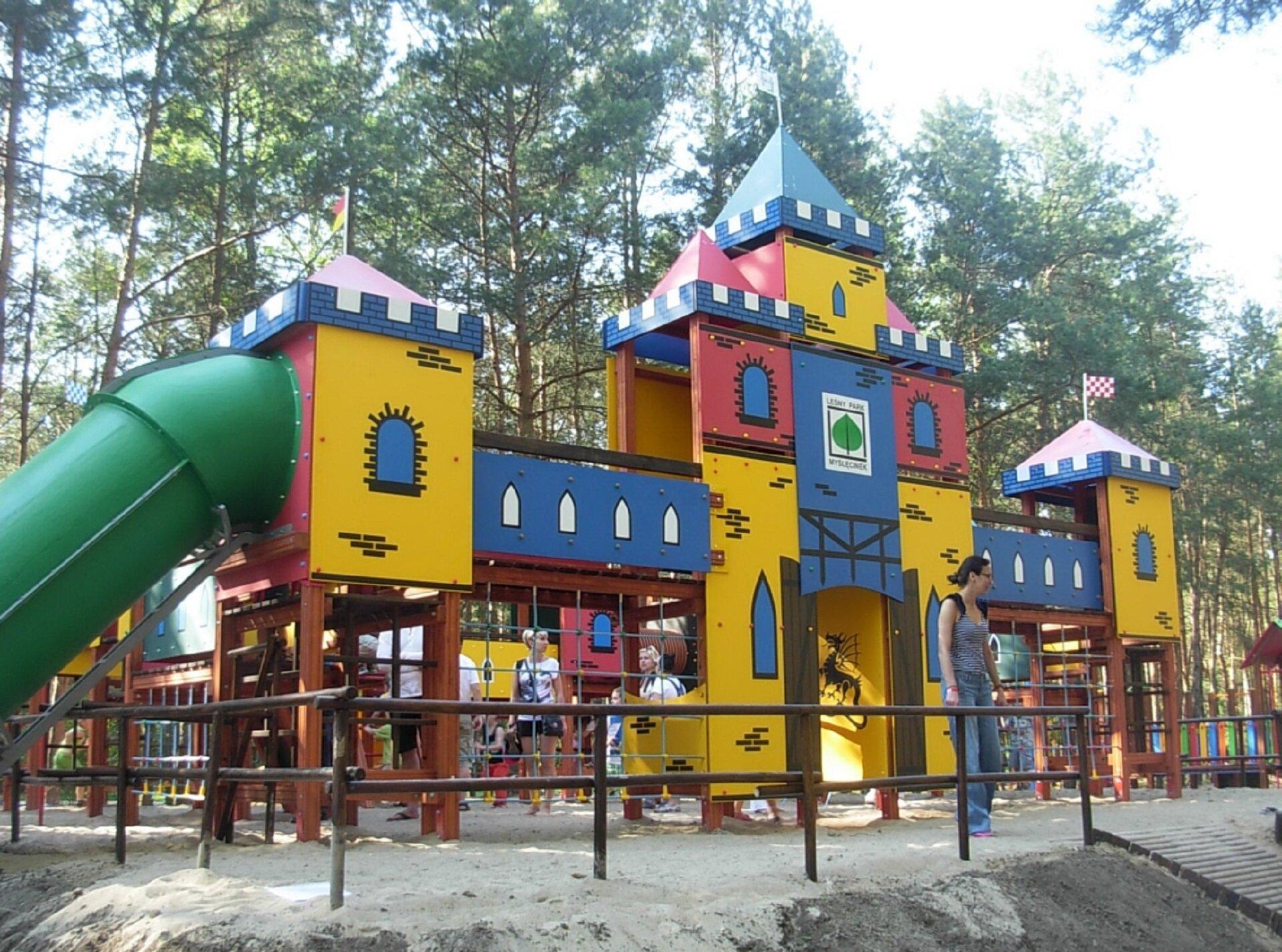 """Ilustracja przedstawia plac zabaw wLeśnym Parku Kultury iWypoczynku """"Myślęcinek"""" wBydgoszczy. Na zdjęciu ukazana jest drewniana, stylizowana na zamek budowla dla dzieci zdrabinkami izieloną, plastikową zjeżdżalnią. Elementy konstrukcji zwieńczone są spiczastymi daszkami zchorągiewkami. Na niebiesko-żółto-czerwonych ściankach namalowano okienka. Na dalszym planie znajdują się pozostałe elementy placu zabaw iwysokie, zielone drzewa. Całość otoczona jest drewnianym płotkiem."""