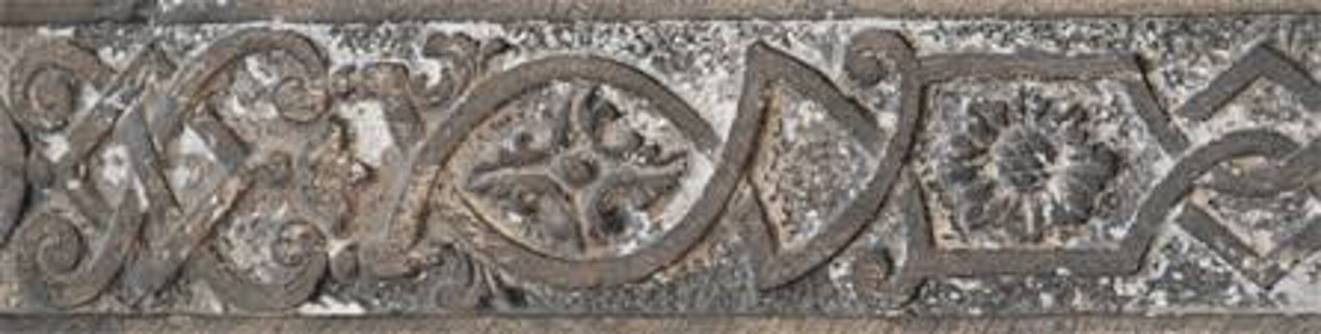 Ilustracja przedstawiająca ornament: wstęgowo-cęgowy. Element dekoracyjny jest wkolorach brązowych.