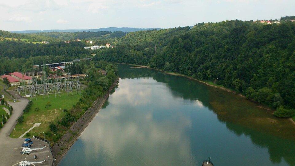 Na zdjęciu szeroka rzeka. Na lewym brzegu zabudowania. Na prawym brzegu las.
