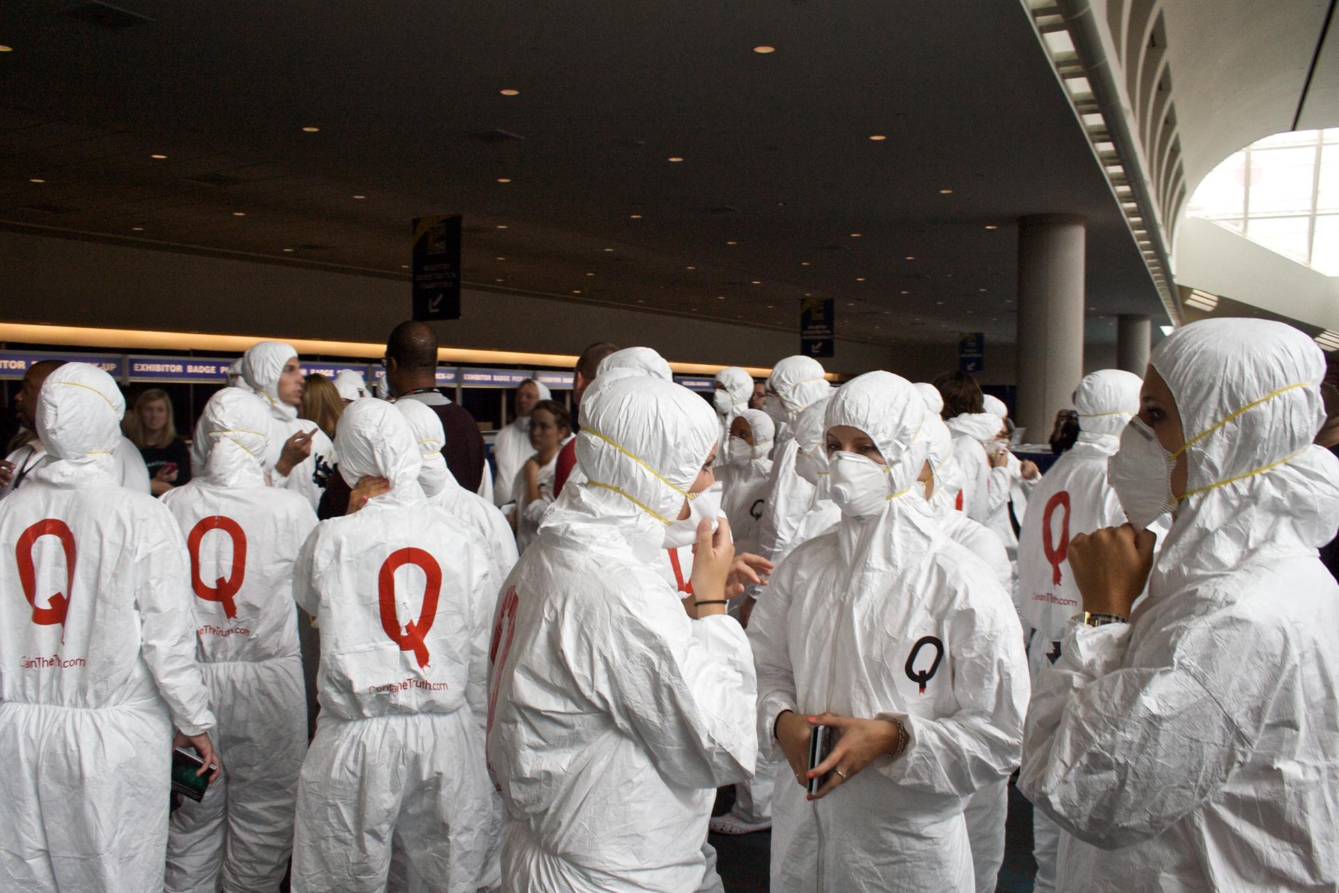 Kolorowe zdjęcie przedstawia grupę osób wbiałych kombinezonach. Wszystkie osoby mają maski nałożone na nos iusta. Na plecach duża czerwona litera Q.