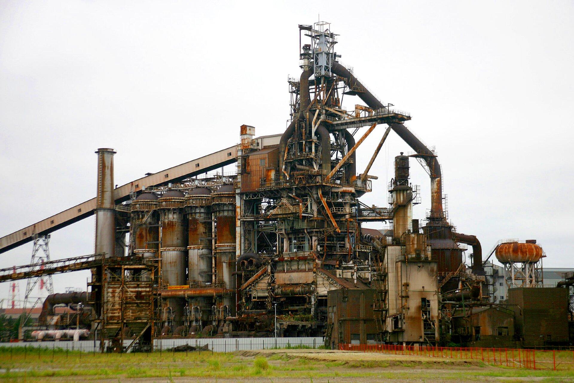 Zdjęcie przedstawia kompleks hutniczy zwidocznym wielometrowym wielkim piecem otoczonym ze wszystkich stron przez platformy, rury itaśmociągi do transportowania surowców.