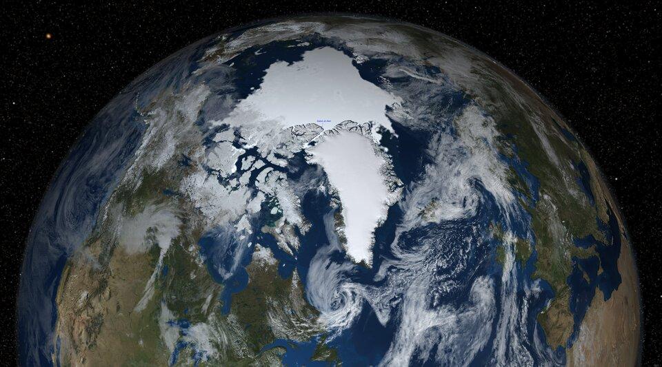 Na zdjęciu satelitarnym fragment kuli ziemskiej. Fotografia od strony bieguna północnego. Widoczne wody wkolorze ciemnoniebieskim, żółto-zielone kontynenty. Białe pierzaste obłoki chmur na całej powierzchni kuli. Na górze kuli ziemskiej biała plama onieregularnym kształcie. To lód pokrywający Ocean Arktyczny iGrenlandia pokryta lądolodem.