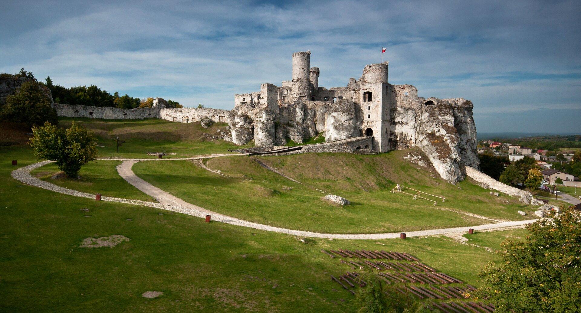 Zdjęcie przedstawia Górę Zamkową. Słoneczny dzień. Na szczycie góry ruiny Zamku Ogrodzieniec. Zamek na środku zdjęcia. Zbocza wzniesienia pokryte wyschniętą trawą. Trawa krótko przycięta. Białe ścieżki dla pieszych na pierwszym planie. Ścieżki otaczają owalnie ruiny zamku zbiałego wapienia. Ściany zamku wbudowane są wskały. Dobrze zachowane trzy wieże to najwyższe części zamku. Wieże wkształcie walca. Na lewo od zamku długi biały mur. Na prawo od zamku, wgłębi zdjęcia, widoczne zabudowania współczesnego miasteczka.