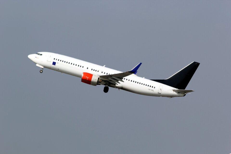 Zdjęcie przedstawia samolot pasażerski na tle nieba. Niebo stalowoniebieskie. Samolot bały, widok na lewy bok. Silnik częściowo pomalowany na czerwono. Końcówki skrzydeł ciemnoniebieskie. Dziób samolotu zwrócony ku górze.