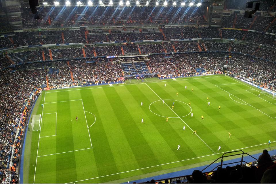 Galeria składa się zpięciu zdjęć prezentujących przykłady imprez masowych. Zdjęcie numer cztery przedstawia mecz piłki nożnej na zielonej murawie. Wokół boiska trybuny stadionu wypełnione tysiącami kibiców. Nad trybunami kilkanaście silnie święcących reflektorów.