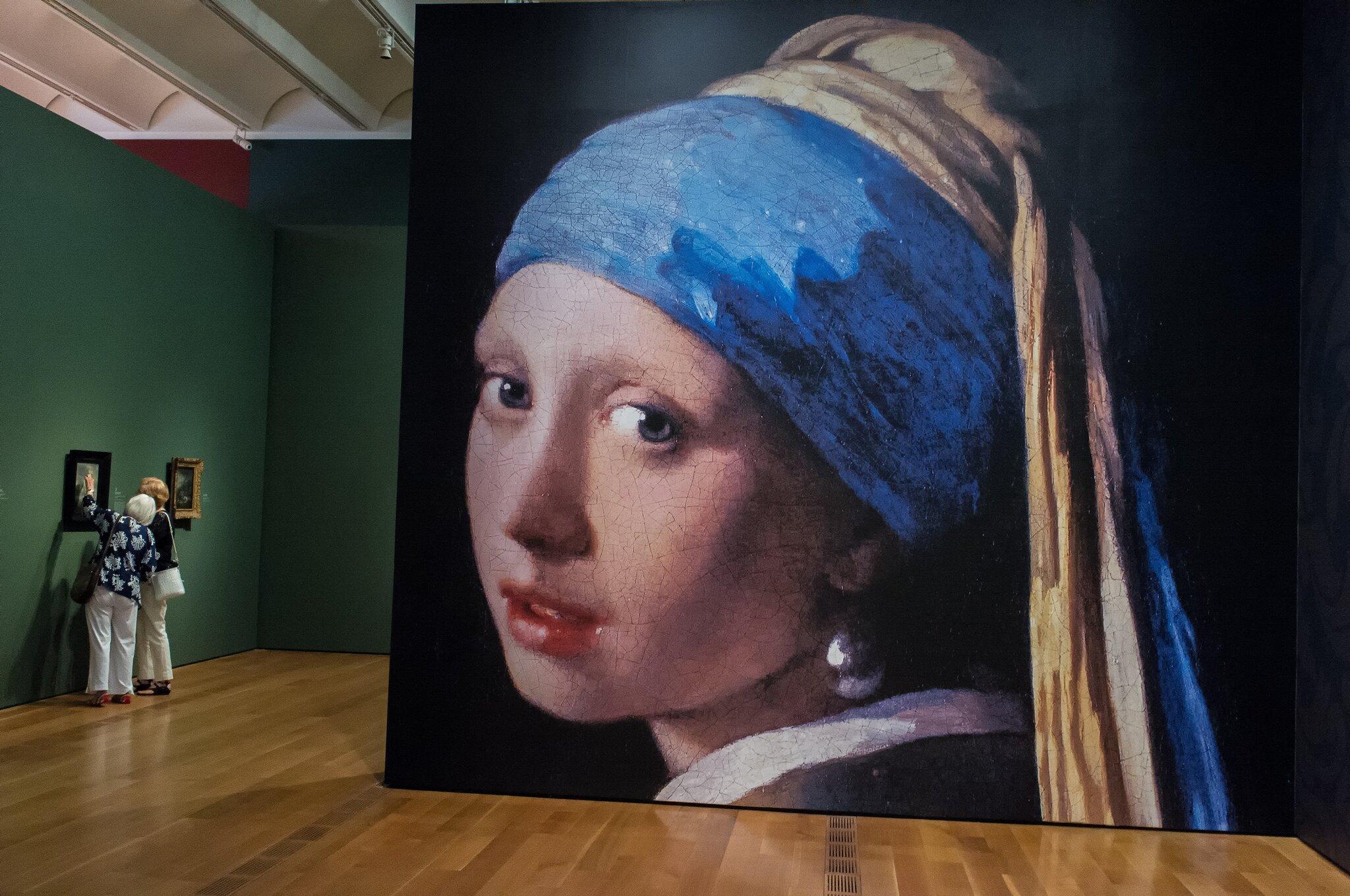 Fragment wystawy wHigh Museum (Atlanta), na pierwszym planie fragmentDziewczyny zperłą Jana Vermeera. Fragment wystawy wHigh Museum (Atlanta), na pierwszym planie fragmentDziewczyny zperłą Jana Vermeera. Źródło: Ralph Daily, fotografia barwna, licencja: CC BY 2.0.