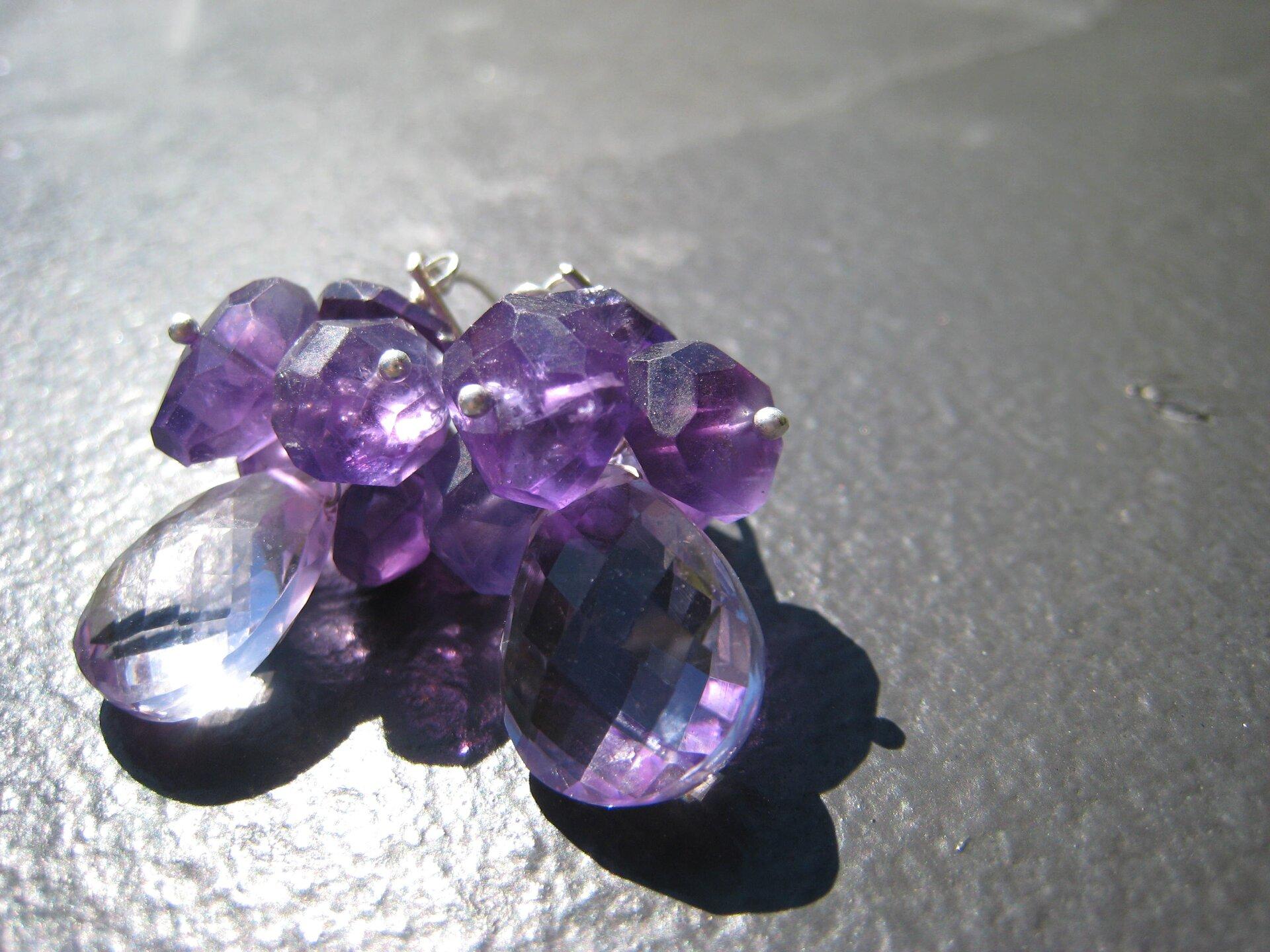 Na zdjęciu widoczna jest biżuteria wykonana zkilkunastu niewielkich ametystów połączonych ze sobą wcoś wrodzaju bukietu. Wszystkie kamienie mają fioletowy kolor, za wyjątkiem silnie podświetlonego po lewej stronie, który wydaje się przezroczysty ibezbarwny. Kamienie połączone są ze sobą za pomocą metalowych drucików.