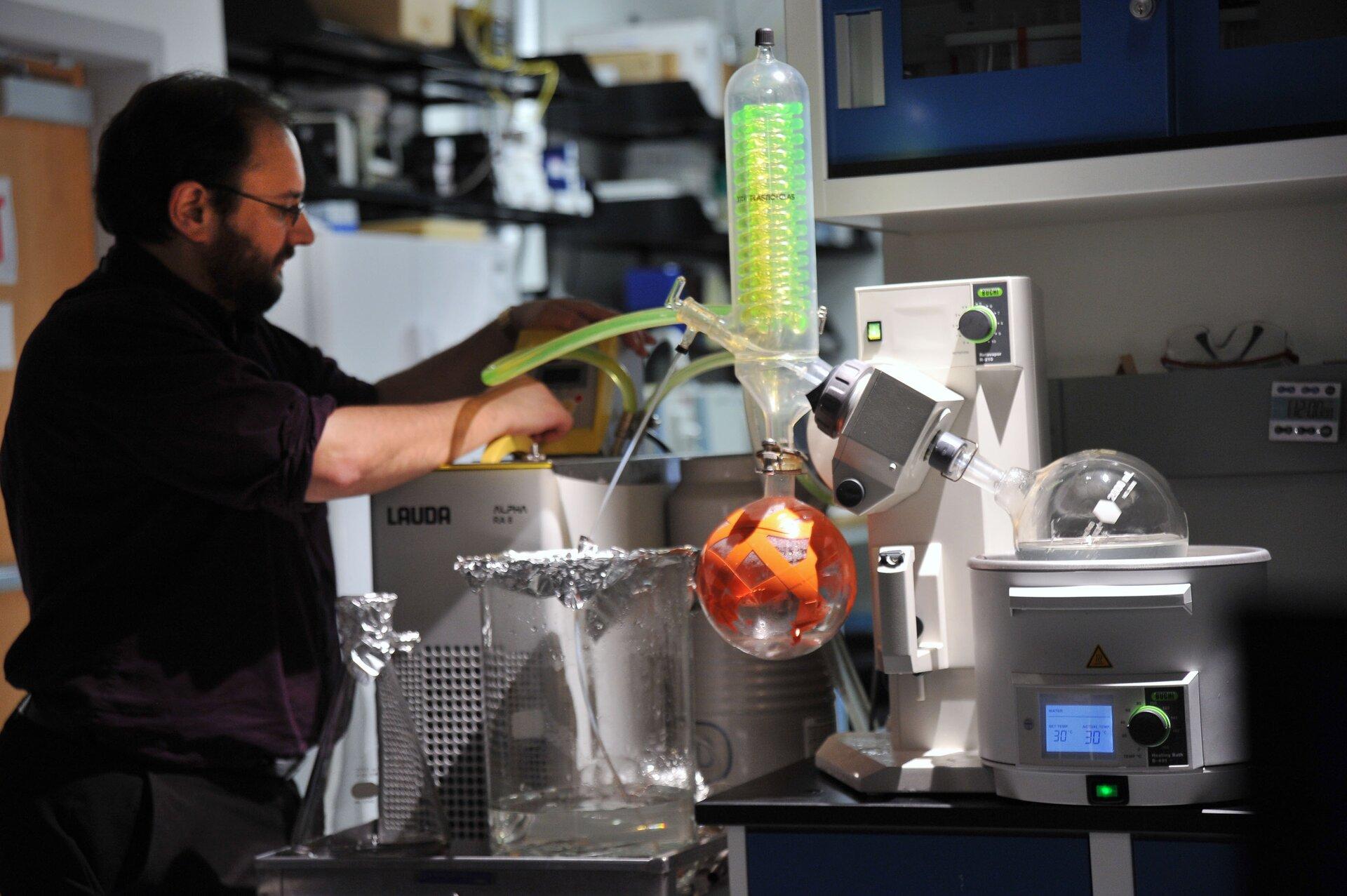 Zdjęcie przedstawia pracownika laboratorium obsługującego duże urządzenie oskomplikowanym wyglądzie. Urządzenie składa się dużego, białego korpusu po prawej stronie fotografii, wktórym wyróżnić można element grzewczy czyli łaźnię, wktórej spoczywa ustawiona pod kątem około czterdziestu pięciu stopni duża kolba kulista zogrzewanym roztworem. Łaźnia sterowana jest elektronicznie, pod kolbą znajduje się panel zwyświetlaczem LCD. Szyja kolby unieruchomiona jest wuchwycie, który podczas podgrzewania obraca kolbę. Po drugiej stronie uchwytu umocowana jest nieruchomo aparatura szklana przy której stoi laborant. Zestaw ten składa się, licząc od dołu, zmałej kolbki będącej odbieralnikiem odparowanej cieczy oraz tak zwaną chłodnicą zwrotną wktórej płyn chłodzący wspiralnej rurce charakteryzuje się zielonkawą barwą. Zadaniem chłodnicy zwrotnej jest wyłapywanie par uciekających zdużej kolby, chłodzenie ich iskraplanie tak, aby zbierały się wmałej kolbie odbieralniku. Od elementu szklanego łączącego ze sobą obie kolby ichłodnicę odchodzi wlewo jeszcze jedna rurka wyposażona wkran połączona zpompą.