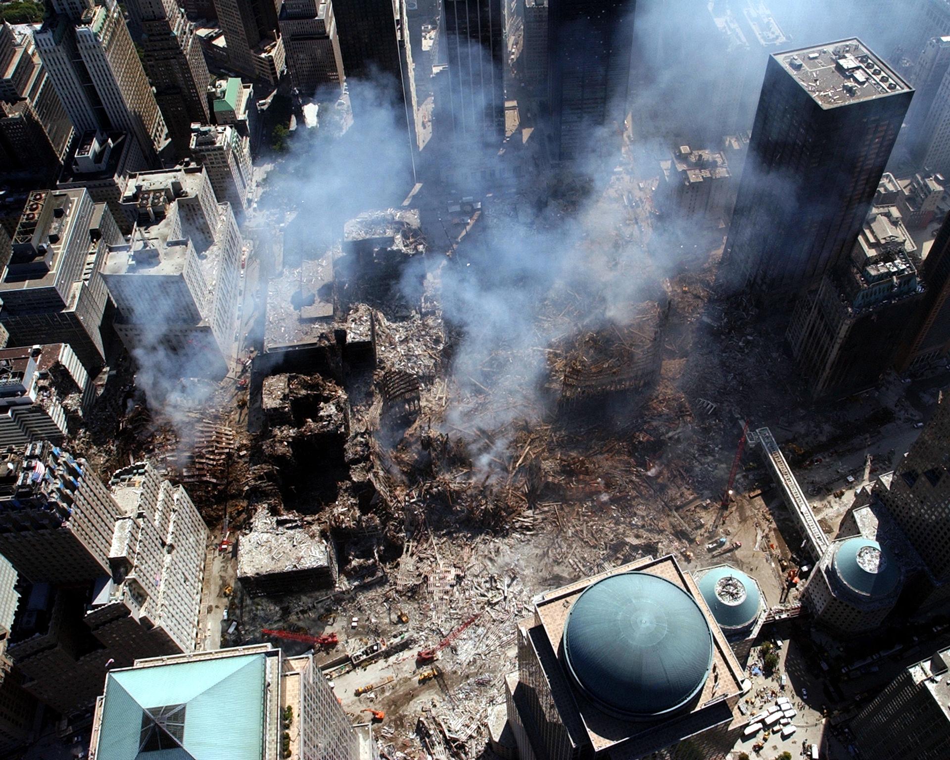 Kolorowe zdjęcie zgóry, przedstawia puste miejsce po ataku na wieże WTC. Miejsce znajduje się wcentrum Nowego Jorku. Wokół miejsca gdzie stały 2 wieże znajdują się budynki. Niektóre częściowo nadpalone izniszczone. Miejsce jest puste miejsce pokryte gruzem, wygiętymi metalowymi resztkami budynku. Nad zwałami gruzu unosi się biały przeźroczysty dym.