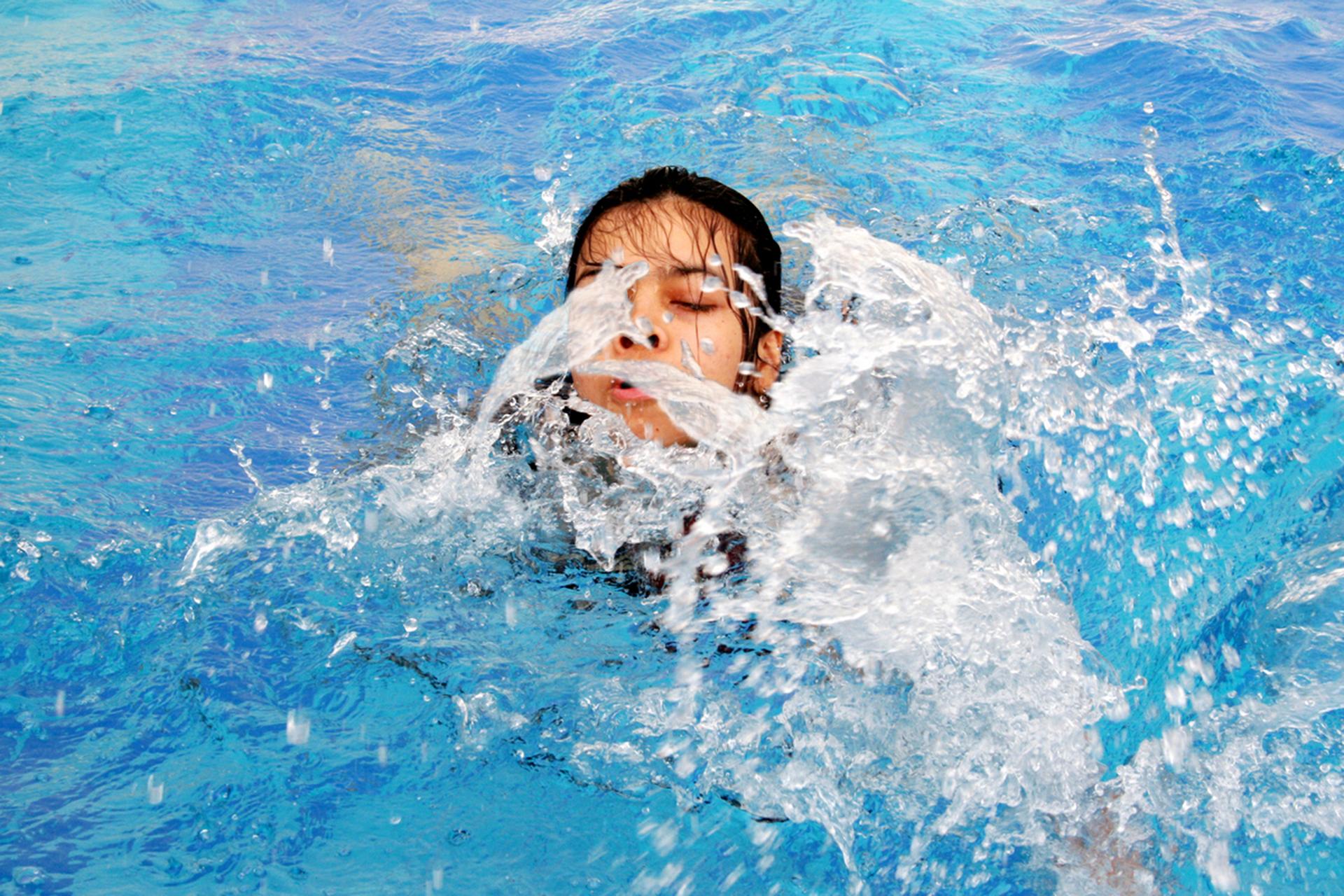 Kolorowe prostokątne zdjęcie przedstawia nastolatkę wbasenie. Czysta błękitna woda. Nastolatka ma mokre ciemne włosy. Zamknięte oczy. Mocno to rozszerzone nozdrza. Wokół twarzy białe rozpryskujące wróżnych kierunkach krople wody.