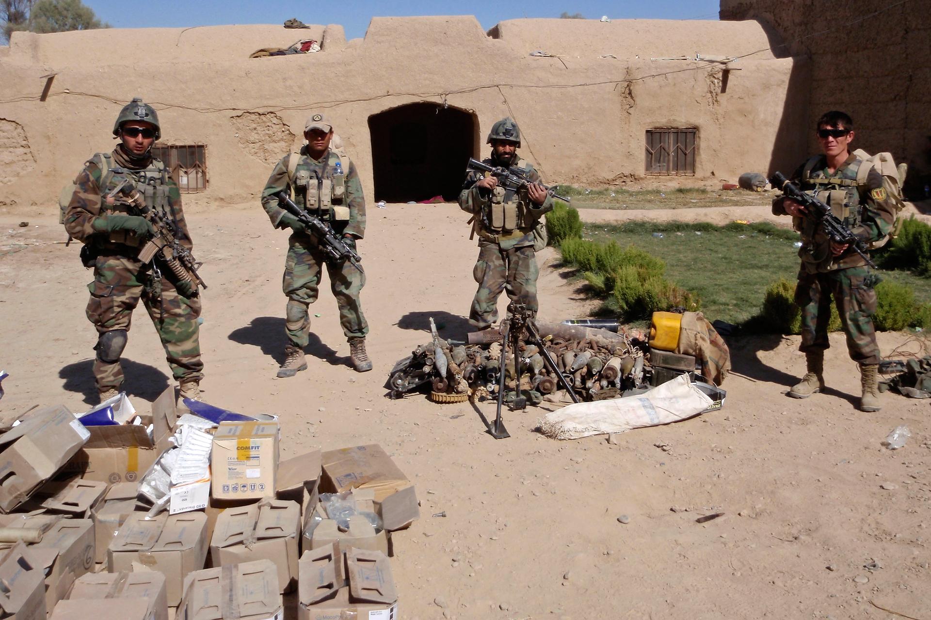 Zdjęcie przedstawia przechwycenie nielegalnej broni. Słoneczny letni dzień. 4 żołnierzy pilnuje przechwyconą broń wmałej wiosce na Bliskim Wschodzie. Na pierwszym planie pudełka znielegalną bronią. Na placu przed wiejskim glinianym domem żołnierze stoją trzymając karabiny.