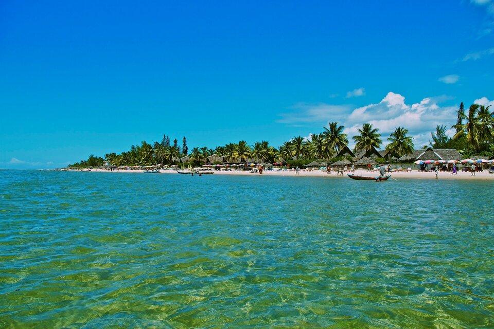 Na zdjęciu na pierwszym planie morze, dalej brzeg morza, piaszczysta plaża, palmy, zabudowania zdachami krytymi słomą lub palmowymi liśćmi.