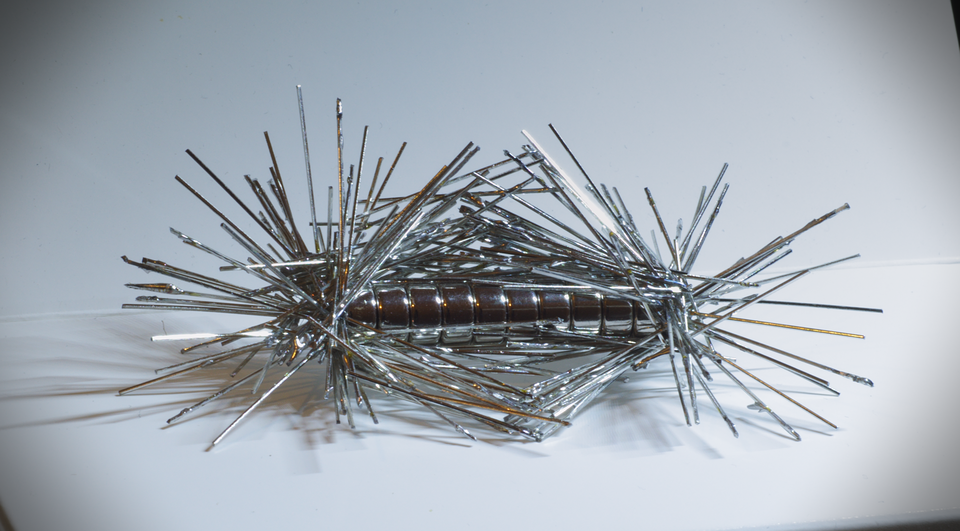 Zdjęcie drobnych przedmiotów (spinaczy, szpilek) przyciągniętych przez magnes