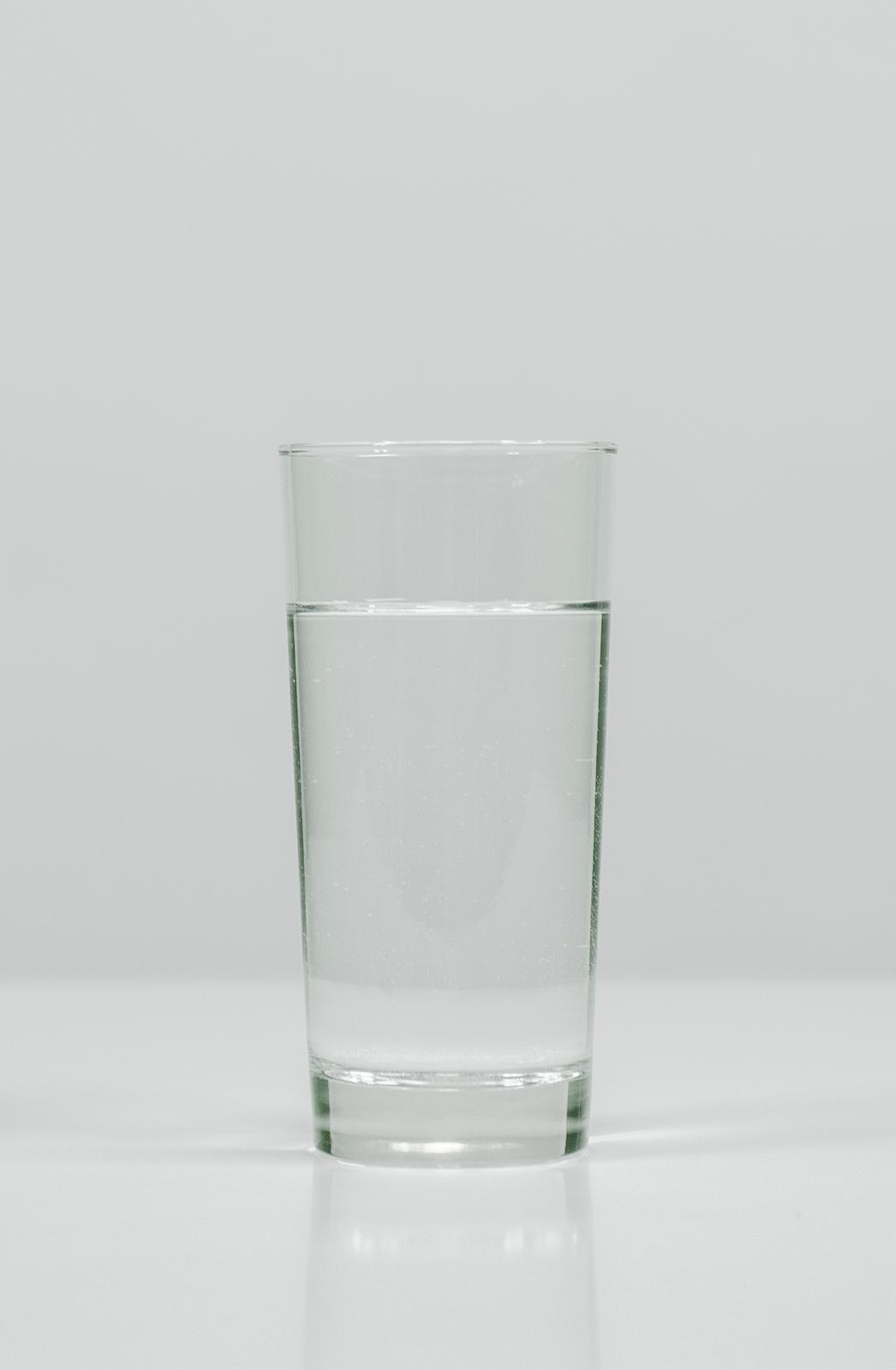 Czarno-białe zdjęcie przedstawia szklankę zwodą stojącą na płaskiej, jasnej powierzchni. Zawartość szklanki jest klarowna, woda wygląda na idealnie czystą.
