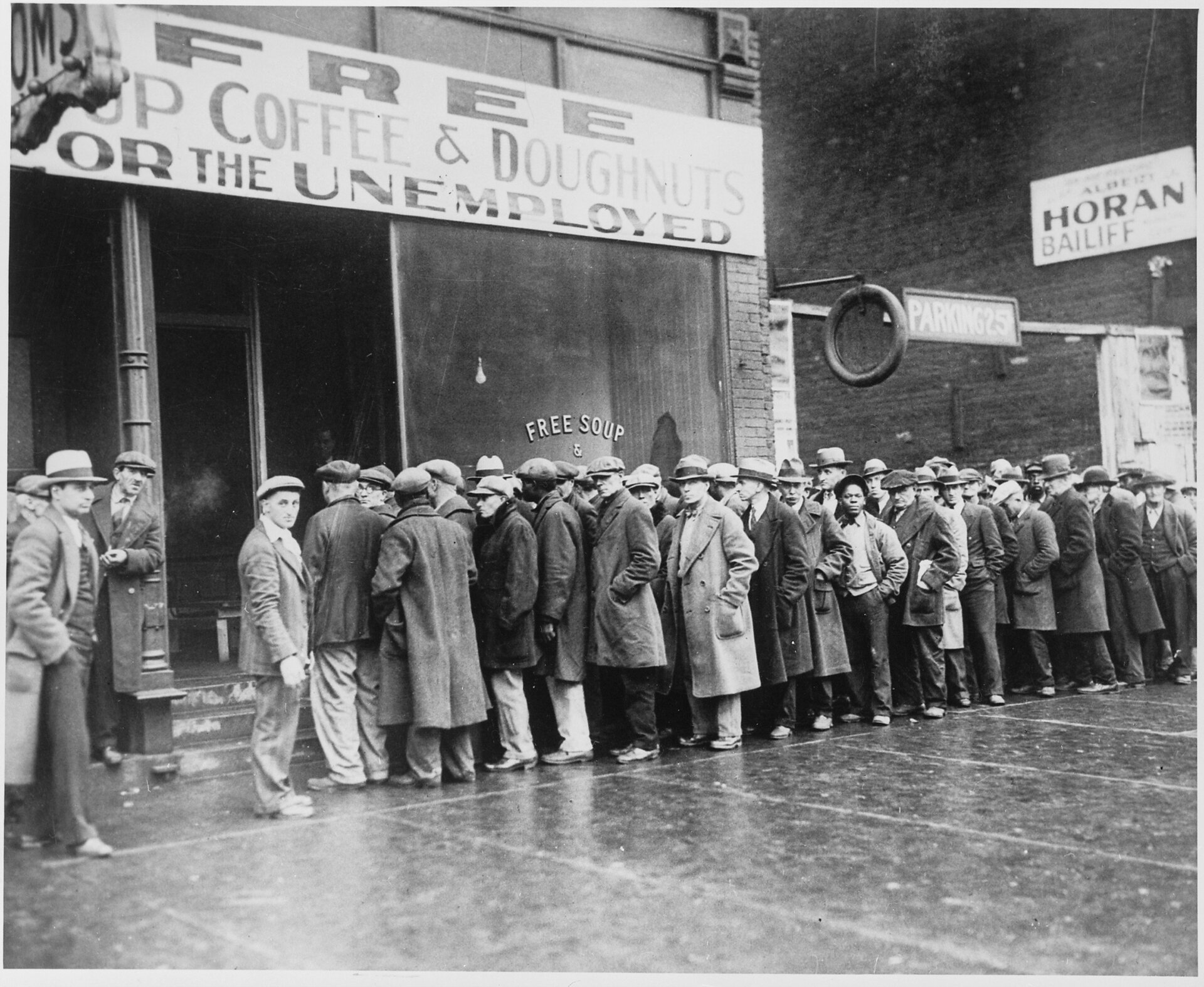 Bezrobotni czekają wkolejce na darmową zupę Źródło: National Archives and Records Administration, College Park , licencja: CC 0.
