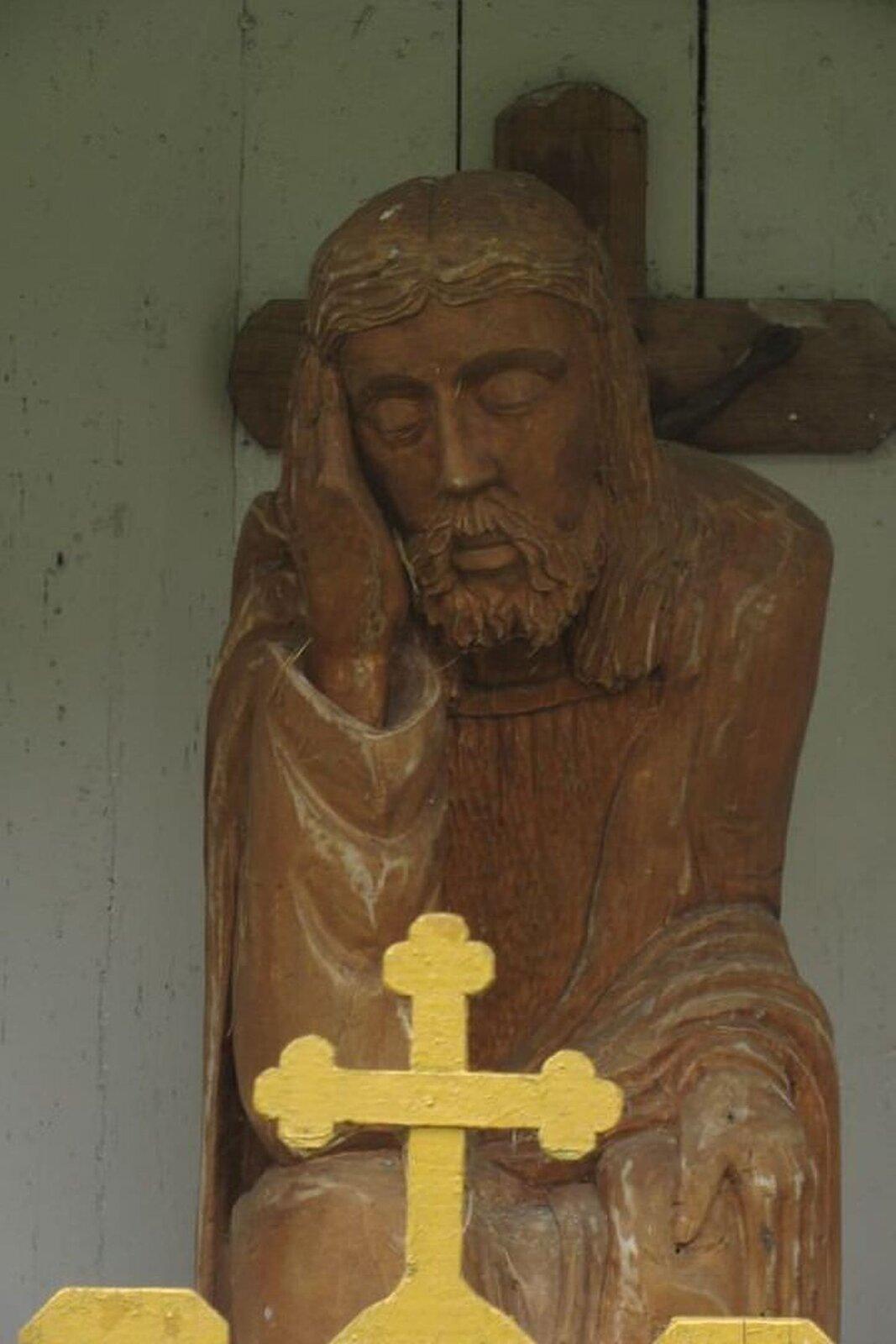 """Ilustracja przedstawia drewnianą rzeźbę """"Chrystusa frasobliwego"""". Ukazuje Jezusa zzamkniętymi oczami. Jest ukazany wpozycji siedzącej, prawą ręką podpiera głowę, lekko pochyloną wlewą stronę. Za nim znajduje się krucyfiks zawieszony na białej ścianie zdesek."""