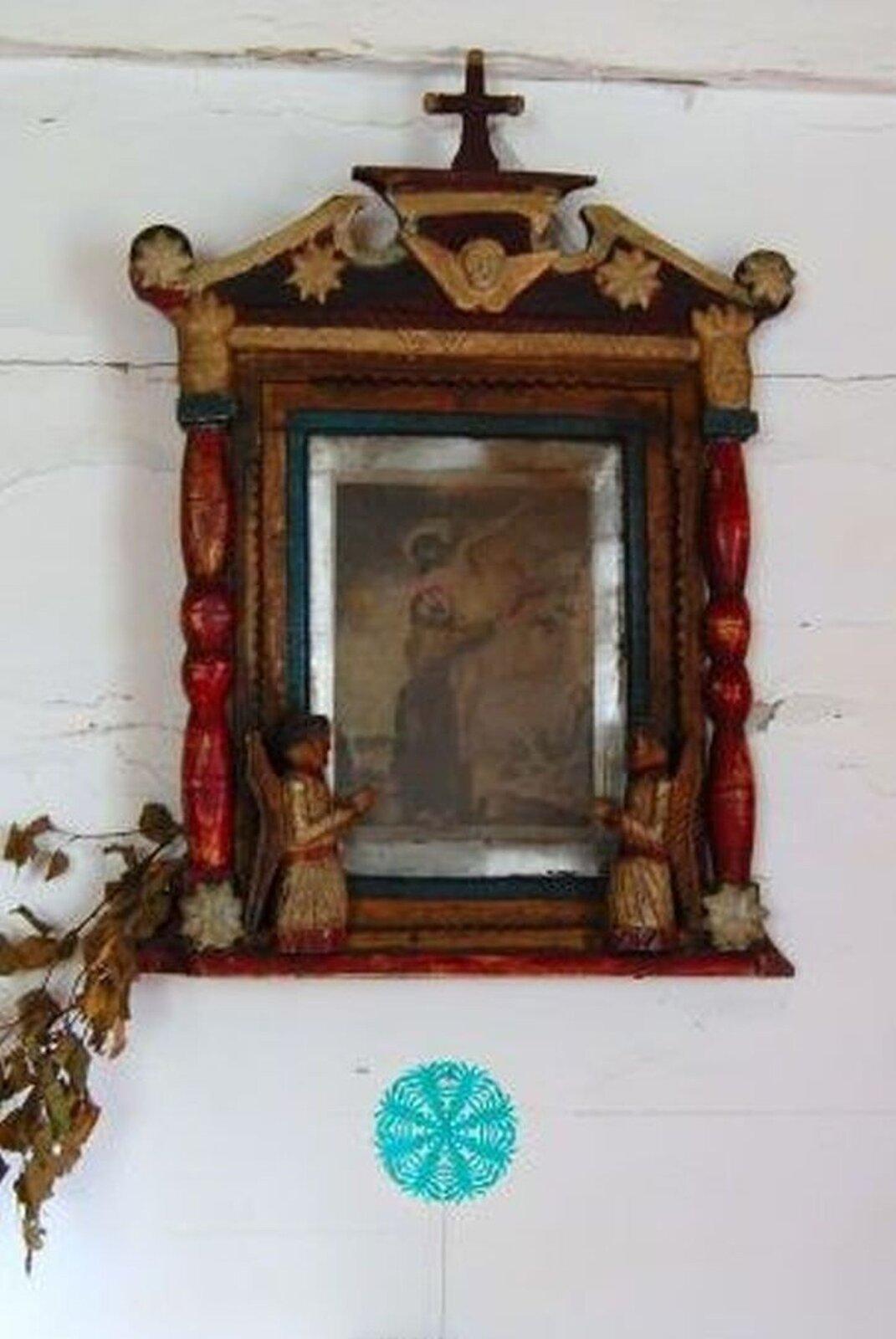 """Zdjęcie przedstawia kapliczkę szafkową. Ukazuje obraz """"Zdjęcie zkrzyża"""". Kapliczka po bokach dekorowana jest czerwonymi kolumienkami. Ugóry zdobi ją nadstawa wkształcie przerwanego tympanonu, zwieńczona krzyżem. Wewnątrz tympanonu zamieszczona jest głowa aniołka ze skrzydłami. Udołu, na podstawie klęczą dwa anioły ze złożonymi rękoma."""