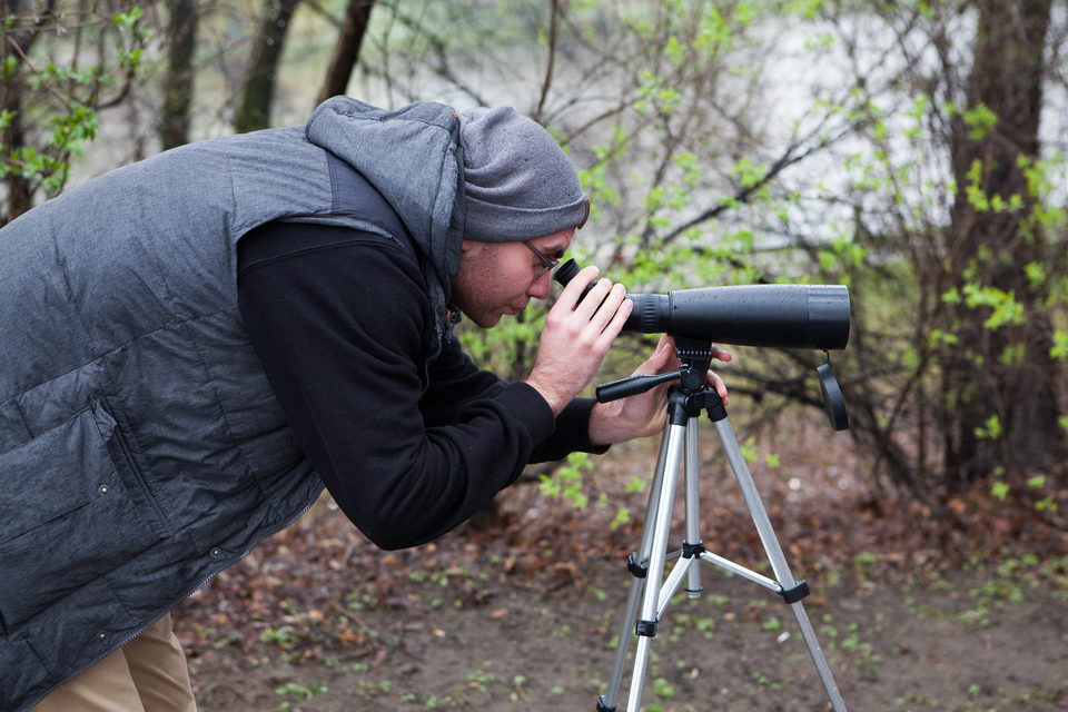 Fotografia człowieka patrzącego przez lunetę na statywie.