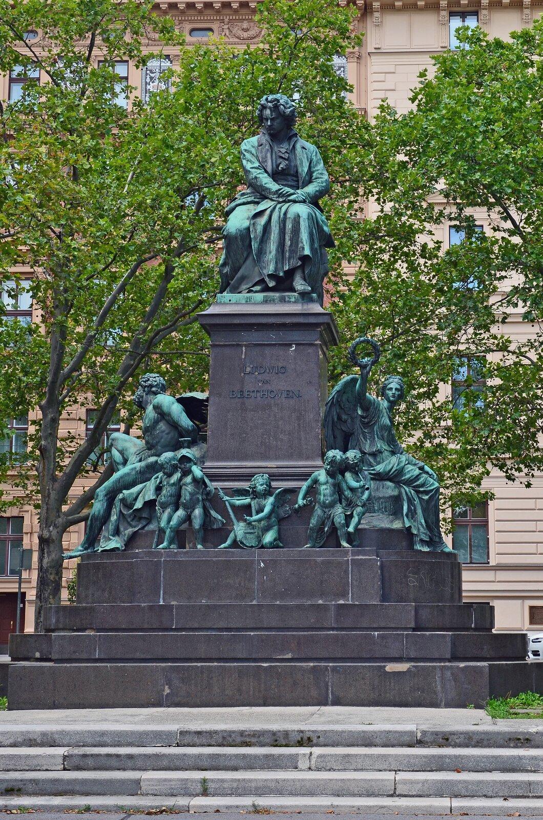 Ilustracja przedstawia pomnik zsiedzącym Ludvigiem van Beethovenem wWiedniu. Mężczyzna wśrednim wieku, ubrany wszaty dostosowane do epoki. Włosy lekko kręcone, do ramion. Poniżej kompozytora znajdują się postaci ze skrzydłami.