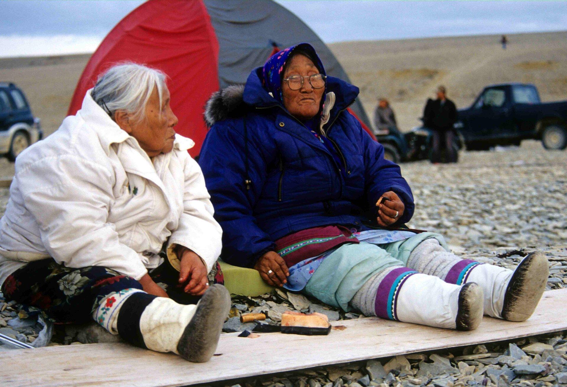 Na zdjęciu dwie starsze kobiety wstrojach zludowymi ozdobami isportowych ciepłych kurtkach siedzą na kamienistej ziemi przed kolorowym namiotem. Wtle zaparkowane samochody terenowe.