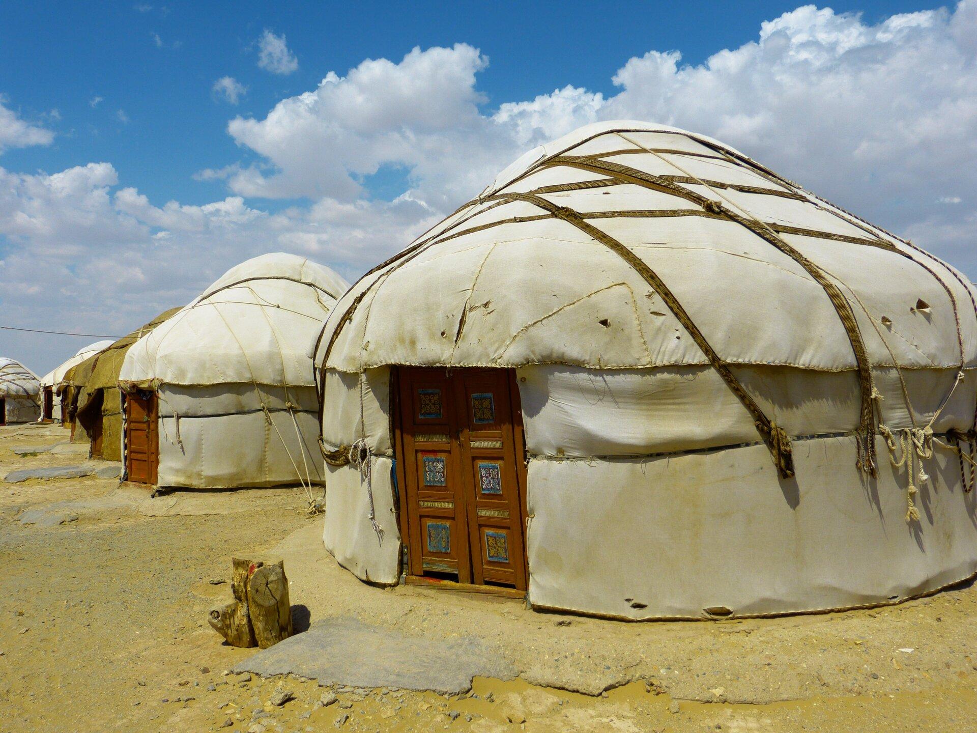 Pierwsza fotografia prezentuje domy mongolskie – jurty. Na fotografii widoczny kilka, stojących jeden za drugim, domów owalnego kształtu przykrytych grubym, białym filcem. Domy mają dach wkształcie kopuły utrzymywany przerzuconymi przez niego sznurami. Od południa każdy dom posiada drewniane ozdobne drzwi.