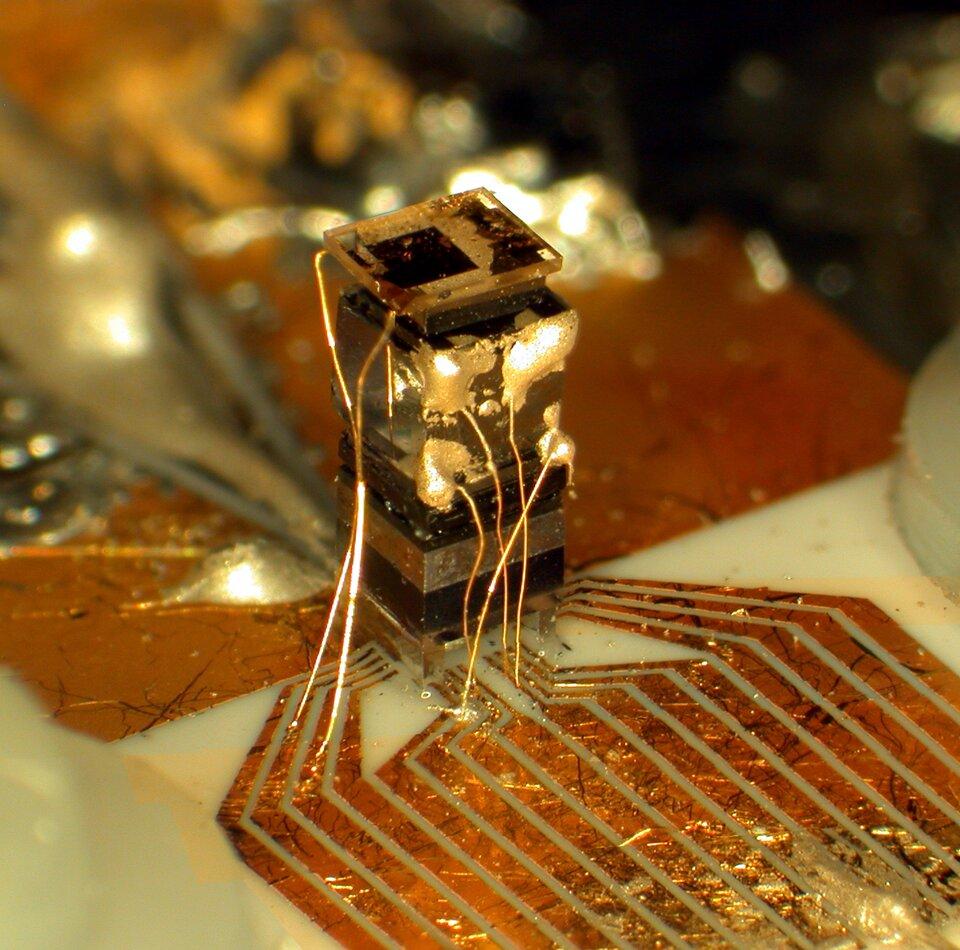 Zdjęcie prezentuje fragment zegara atomowego. Na zdjęciu widoczny jest prostokątny układ scalony, połączony za pomocą lutowanych drucików zpłytą, wktórą wbudowano miedziane szyny.