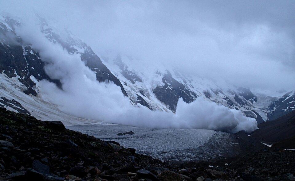 Zdjęcie przedstawia teren górski zimą. Mglisty dzień, mgła zasłania szczyty wysokich gór od około jednej trzeciej wysokości kadru. Zbocza gór są skaliste, czarne. Połacie śniegu pokrywają dużą powierzchnię stromych stoków. Na pierwszym planie teren pokryty czarnymi kawałkami kamieni. Na środku zdjęcia lawina śnieżna przemieszcza się zwysokiego zbocza wdół, czemu towarzyszą tumany wzbitego śniegu