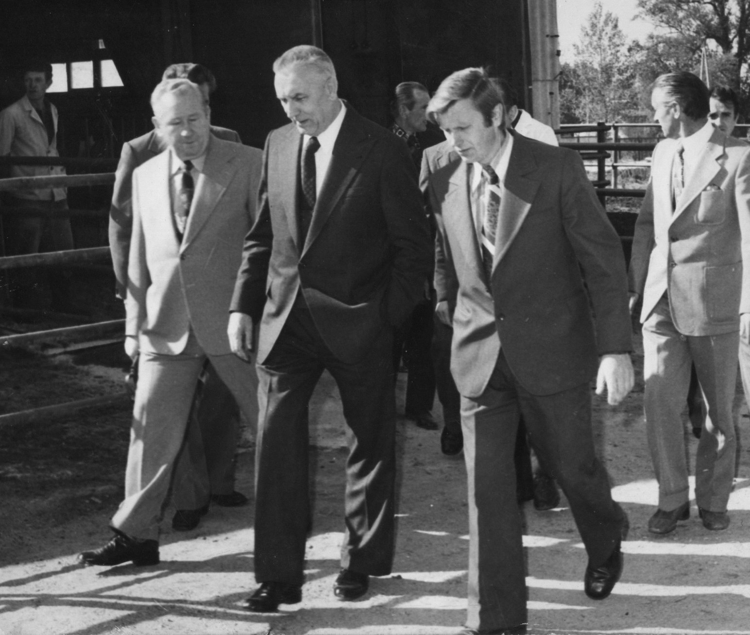 Fotografia czarno-biała przedstawiająca Edwarda Gierka spacerującego wotoczeniu swoich doradców, rozmawiającego znimi.