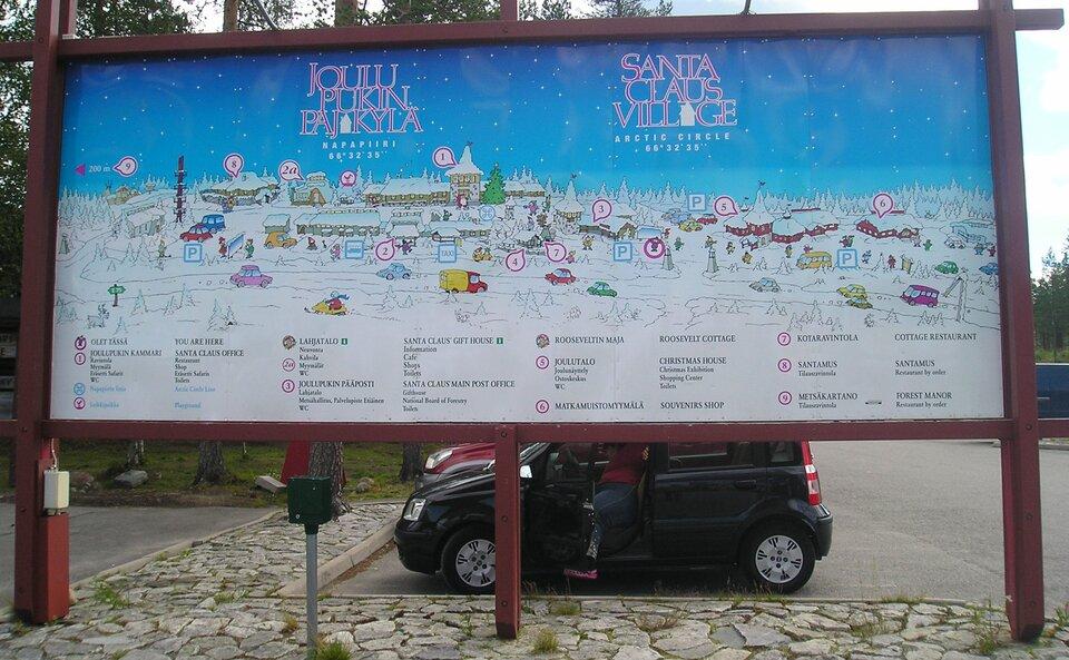 Na zdjęciu plan wioski św. Mikołaja umieszczony na drewnianej tablicy na parkingu. Na planie narysowane ponumerowane budynki opisane wlegendzie.