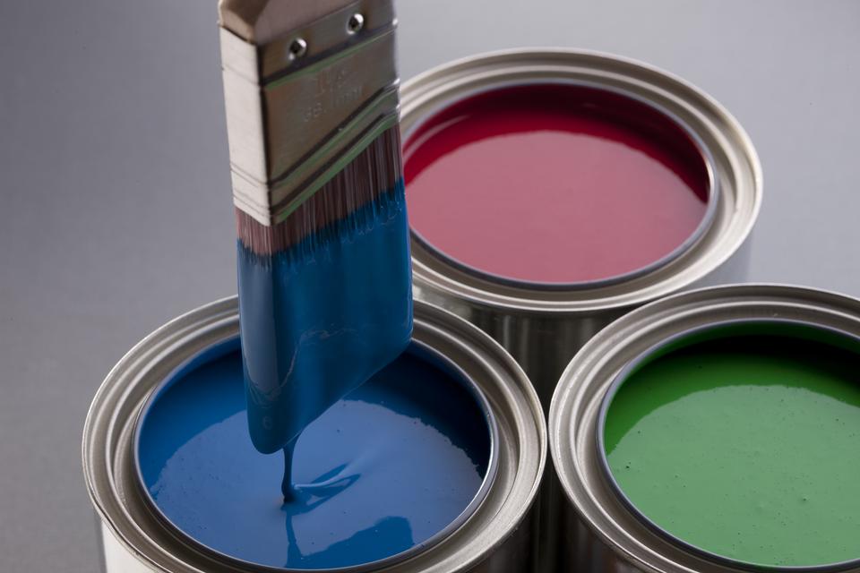 Na fotografii znajdują się trzy otwarte puszki farby: zielona, czerwona iniebieska. Wniebieskiej farnie zanurzono pędzel.