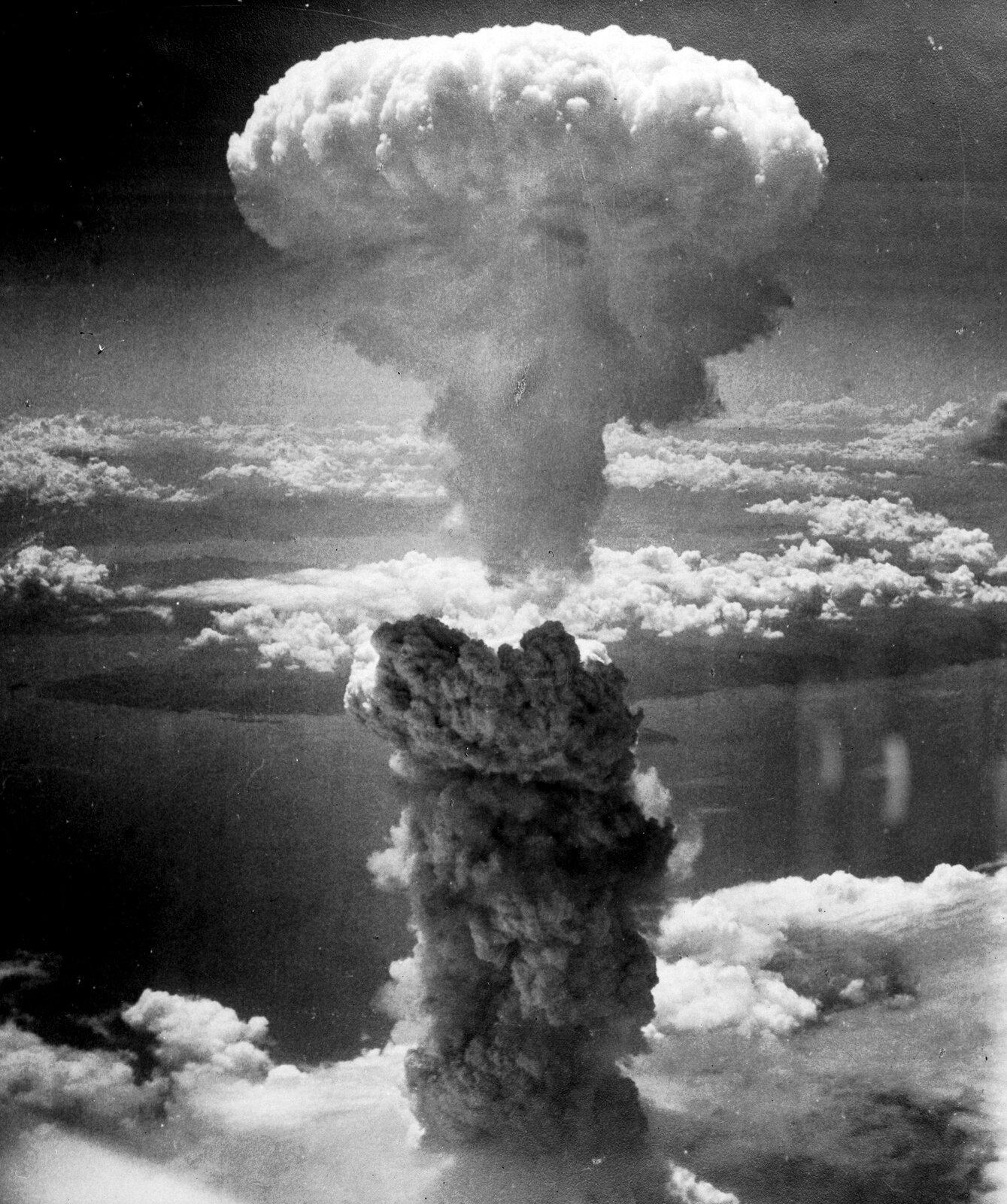 Historyczne zdjęcie czarnobiałe wykonane zpokładu bombowca B-29 przedstawia efekt wybuchu bomby atomowej Fat Man nad Nagasaki. Na pierwszym planie widoczny jest obłok wkształcie grzyba udołu czarny, augóry biały. Daleko poniżej chmury, morze iwyspy. Obszar zktórego wyrasta czarny słup to ląd częściowo przesłonięty chmurami. Brak widocznych szczegółów ukształtowania terenu.