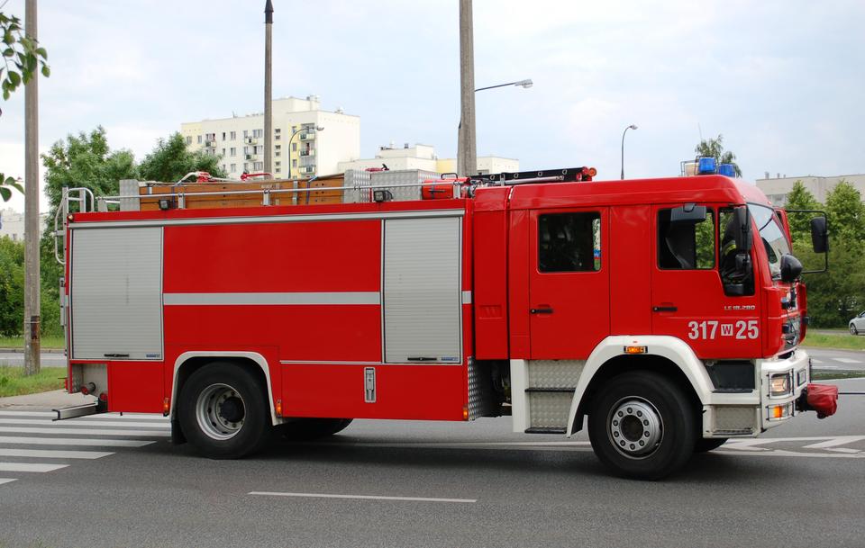 Pierwsze zdjęcie przedstawia czerwony wóz strażacki. Wóz porusza się wprawo, wzdłuż ulicy, prawym bokiem do odbiorcy. Po prawej kabina kierowcy, za kabiną jedno okno imiejsca dla strażaków. Na dachu wozu drabina ułożona równolegle do dachu.