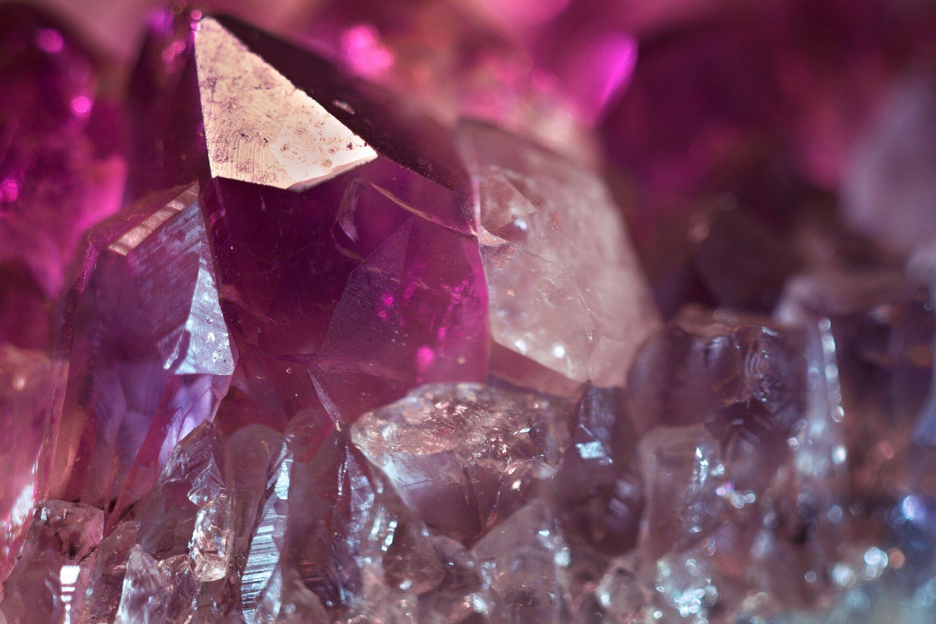 Zdjęcie przedstawia fragment kryształu ametystu wzbliżeniu, na tle pozostałej, większej części minerału. Uwagę zwracają gładkie powierzchnie krystalicznego słupka oraz intensywnie purpurowa barwa kamienia.