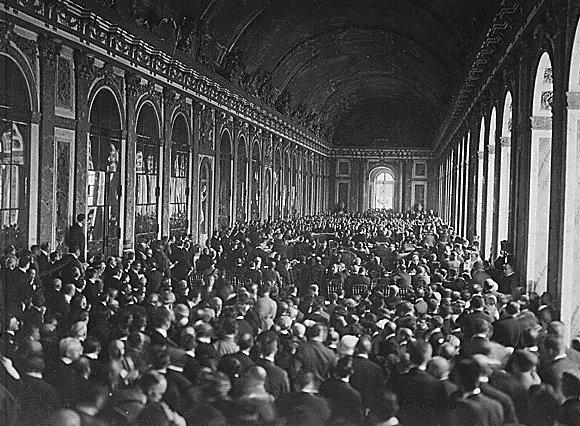 Zdjęcie czarno-białe. Wkorytarzu wPałacu wWersalu, na którego lewej ścianie widać lustra, aprawą ścianę zajmują okna stoi tłum co najmniej kilkuset osób iwszystkie patrzą wkierunku środka korytarza, gdzie przy stołach siedzą mężczyźni. Wtłumie pod ścianami niektórzy stoją na podwyższeniach, zapewne po to, żeby lepiej widzieć.