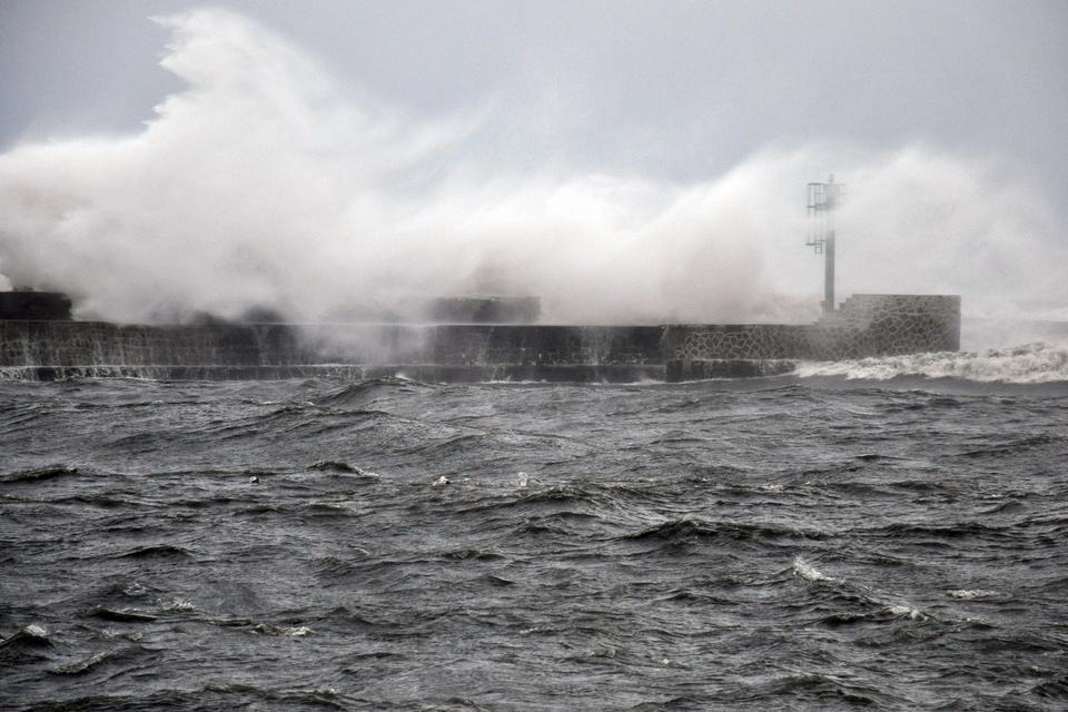 Fotografia prezentuje wygląd wybrzeża morskiego podczas huraganu. Widoczne wzburzone morze oraz fale rozbryzgujące się omolo.