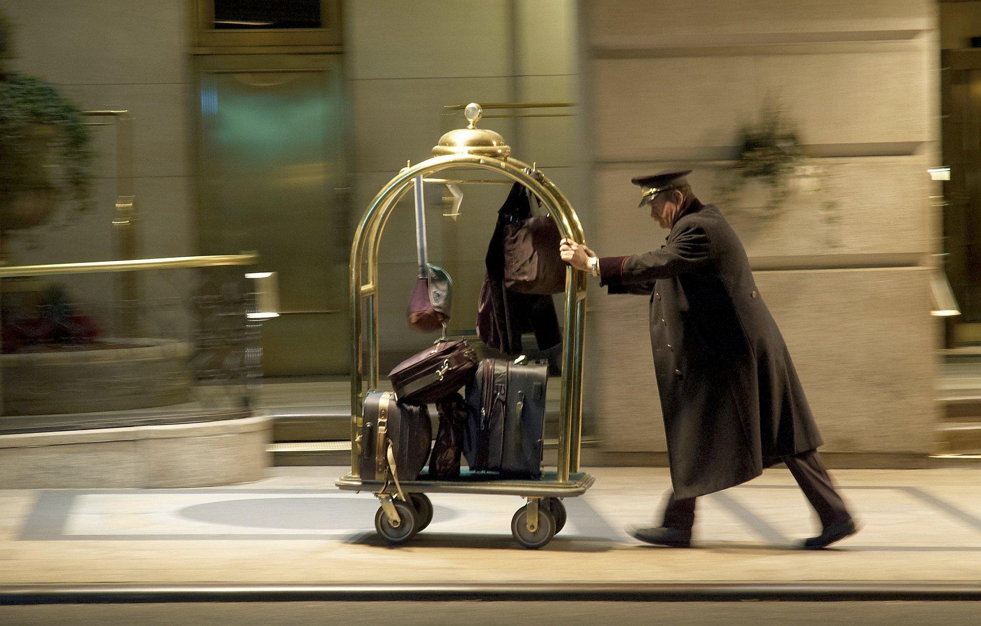 Zdjęcie przedstawia mężczyznę wśrednim wieku ubranego wczarny płaszcz oraz czapkę typową dla pracownika luksusowego hotelu. Mężczyzna idzie chodnikiem pchając przed sobą pozłacany wózek bagażowy wypełniony torbami iwalizkami. Scena uchwycona wruchu, tło za bagażowym rozmyte, akcentuje szybkie tempo przemieszczania się człowieka zwózkiem.